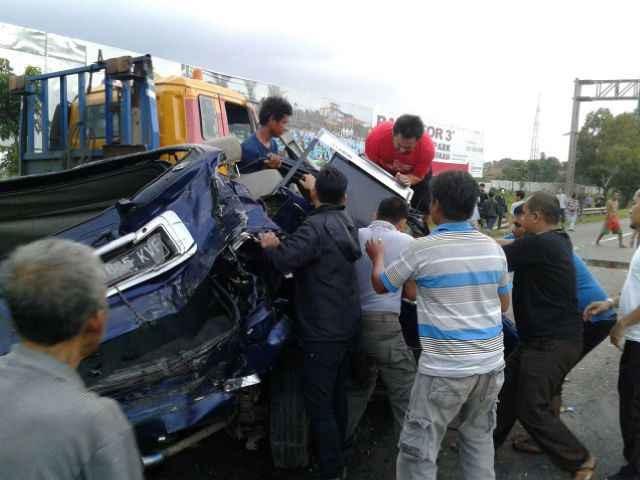Korban terjepit di mobil dan berusaha diangkat.